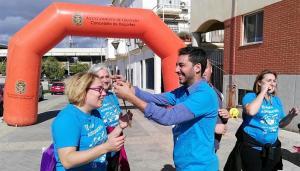 El concejal entrega una medalla a una de las participantes.