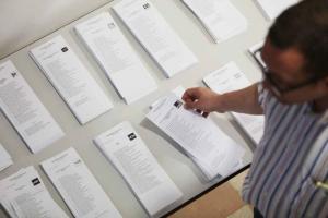 Un elector observa las papeletas en un colegio de Granada capital.