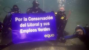 Buzos despliegan una pancarta en el suelo marino.