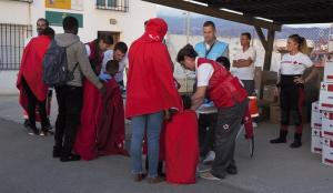 Voluntariado de Cruz Roja presta asistencia a un grupo de migrantes, entre ellos varios menores.