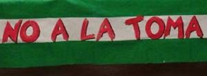 Detalle de una bandera andaluza con el mensaje 'No a la Toma'.