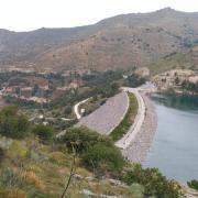 El agua embalsada llega hasta arriba del dique.