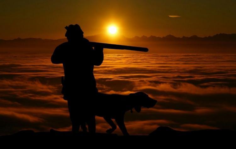 Un hombre cazando con su perro.