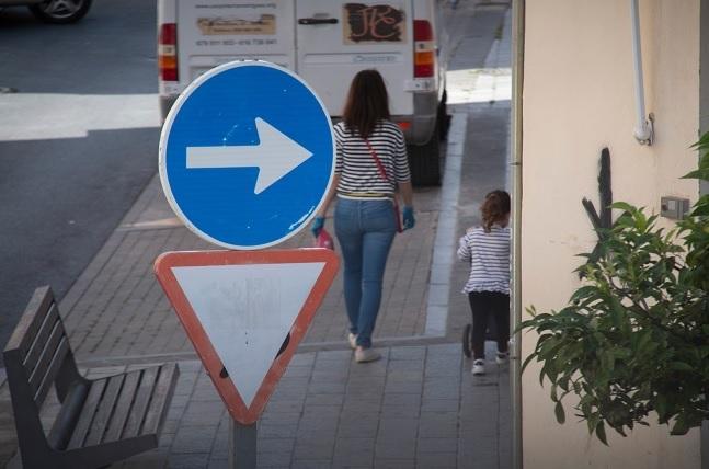 Una mujer pasea con una niña en horario permitido.