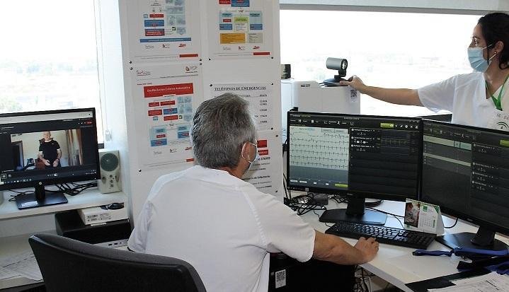 Un médico examina la información cardiaca de un paciente al que sigue en su casa por el monitor.