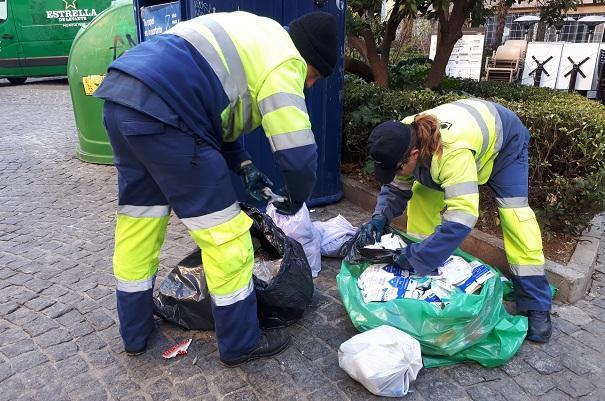 Empleados de Inagra abren bolsas de basura en la vía pública.
