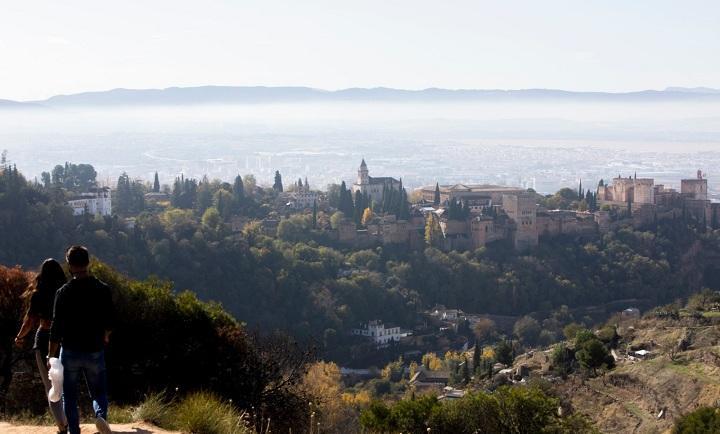 Vista de la Alhambra y detrás la ciudad con su 'boina' habitual'.