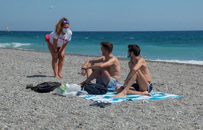 Una vigilante de Cruz Roja conversa con dos bañistas en Playa Granada.