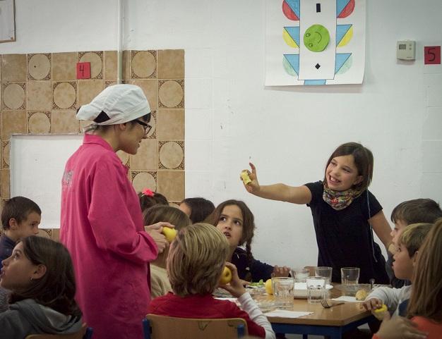 Una niña muestra al personal de cocina que se ha comido una manzana.