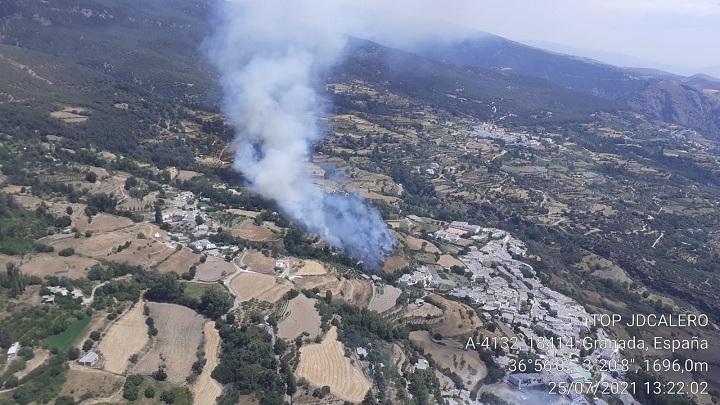 Vista aérea del fuego, muy cerca de los pequeños núcleos de viviendas que componen el municipio de La Taha.