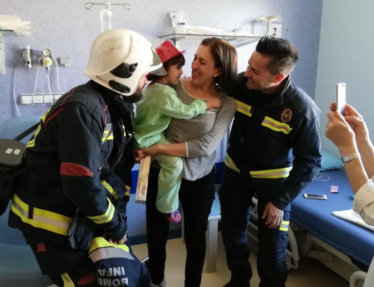 La pequeña Elena sonríe con el casco de bomberos.