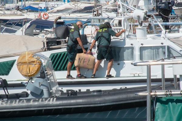Dos agentes sacan de la embarcación el fardo de hachís.