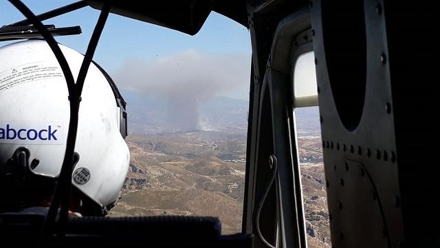 Un helicóptero se dirige a la zona del fuego, al fondo.