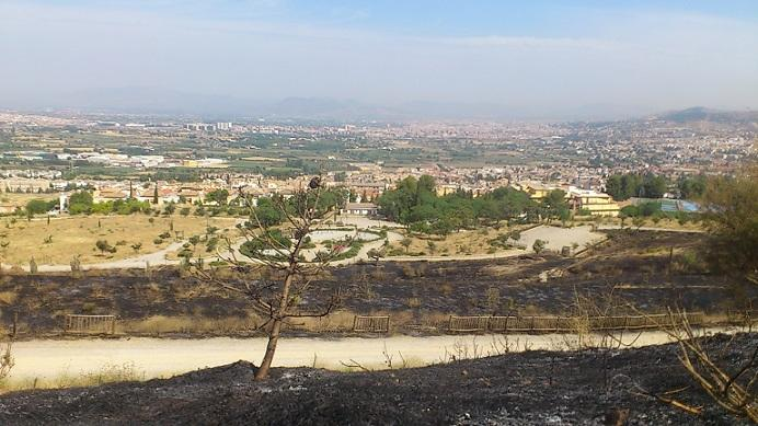 Efectos del fuego del viernes pasado en Cájar, con Granada y su nube de polución al fondo.