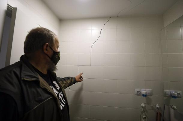 Un vecino señala una grieta en el baño de su vivienda, en Atarfe.