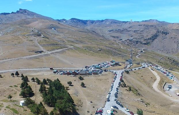 Vista de la Hoya de la Mora, repleta de vehículos, con el Veleta al fondo.