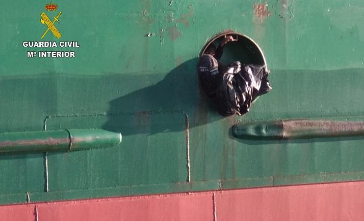 El menor, en el hueco de una bita de amarre del buque.