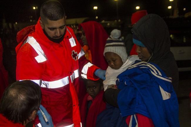 En la imagen, Cruz Roja atiende a las personas rescatadas a su llegada, de madrugada, al Puerto de Motril.