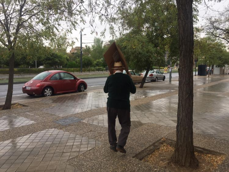 La lluvia le sorprende y debe guarecerse bajo un cartón.