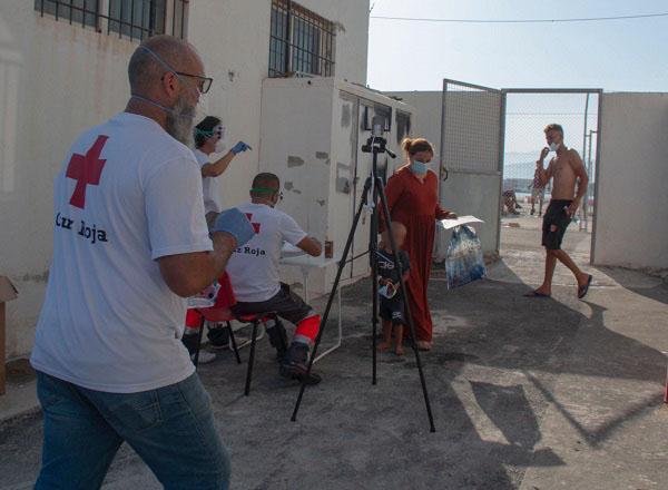 Voluntariado de Cruz Roja toma la temperatura y presta una primera asistencia a los migrantes.