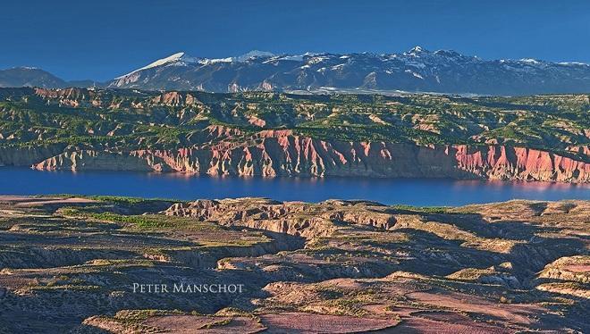 Pantano del Negratín y 'badlands', en el Geoparque, con Sierra Nevada al fondo.