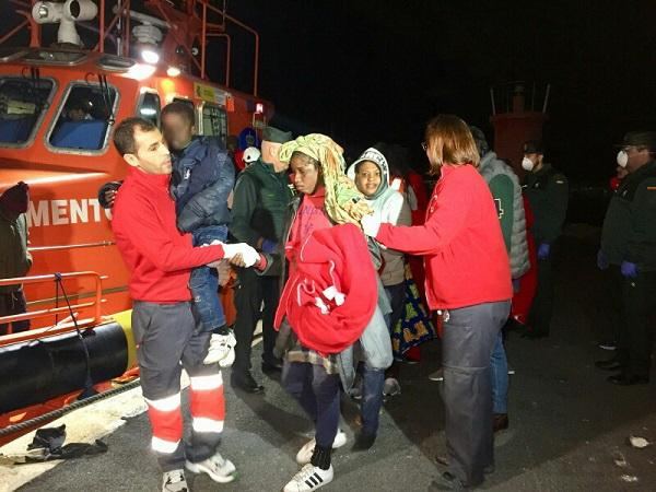 Voluntarios de Cruz Roja atienden a las personas rescatadas, entre ellas un niño.