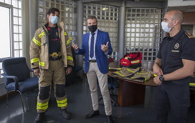 Un bombero, vestido con el nuevo traje, junto al concejal César Díaz.