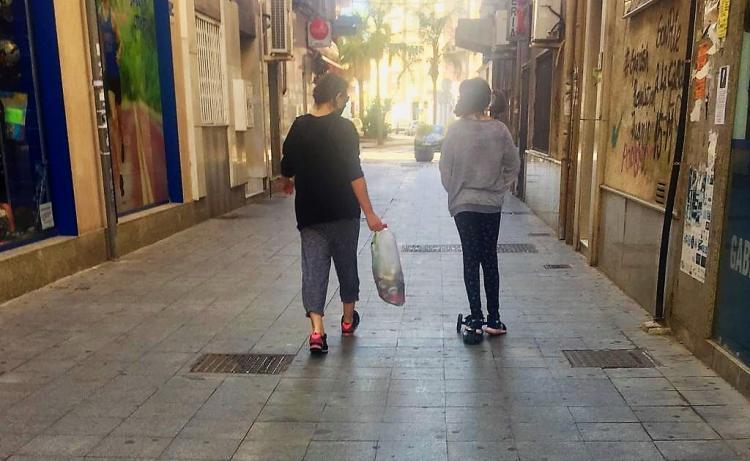 Una niña pasea, acompañada, por una calle de Motril.
