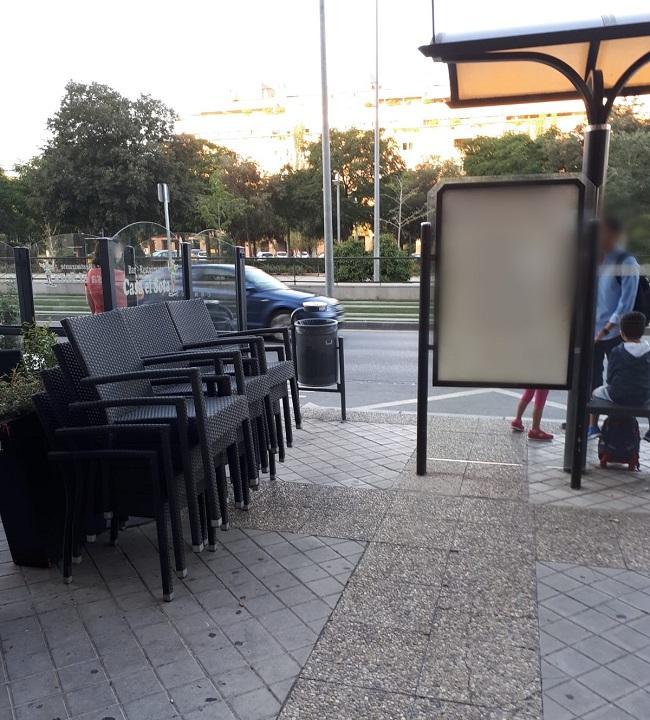 Sillas apiladas junto a la parada de bus.