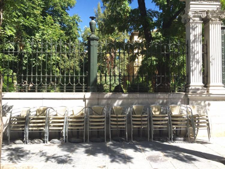 Sillas de una terraza apiladas en una plaza.