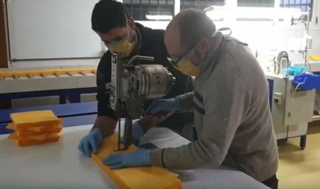 Personal de Toldos Zaidín corte material para hacer las mascarillas.