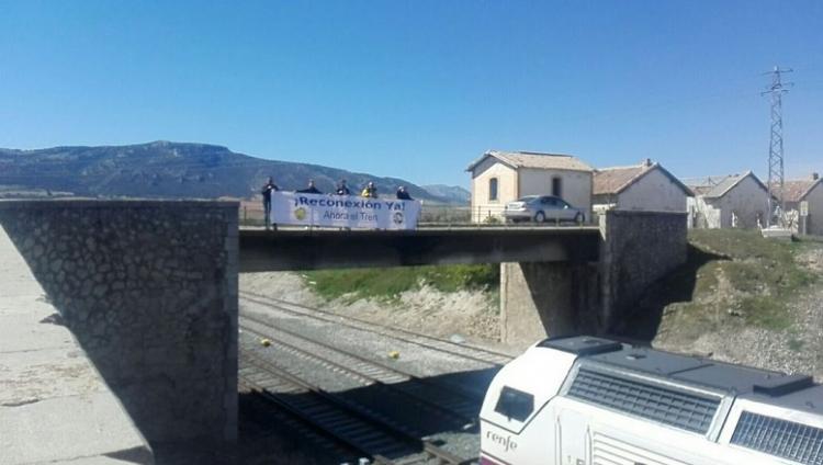 Pancarta pidiendo la reconexión al paso de un tren por Moreda.