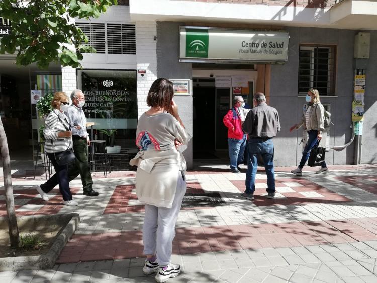 Peatones caminan junto a usuarios del centro de salud Manuel de Góngora, que aguardan su turno a las puertas del recinto.