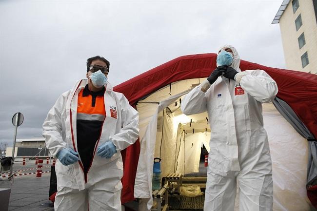 Trabajadores de proteccion civil se desinfectan contra el coronavirus en una carpa instalada en el hospital del PTS de Granada.