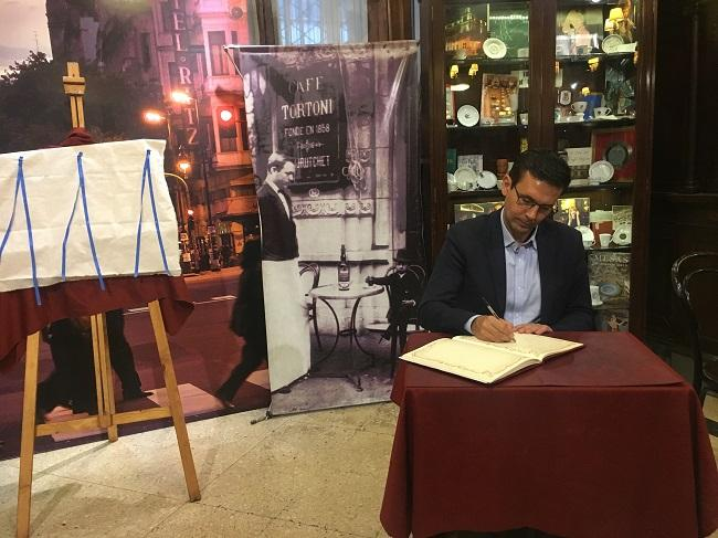 El alcalde firma en el libro del Café Tortoni de Buenos Aires.