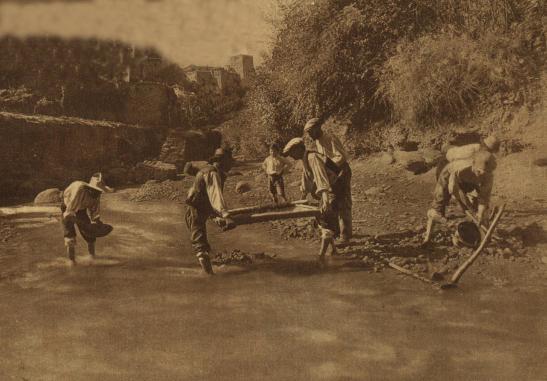 Lavadores de arenas de oro en el río Darro, por debajo del Sacromonte. Al fondo aparece la Alhambra. Esta foto fue hecha en 1930 y publicada en un periódico de Madrid.