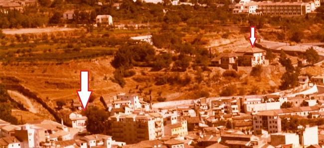 La flecha grande de la izquierda marca el lugar donde estuvo el Carmen y terrenos de la huerta de Lebrija hasta finales del siglo XX. La flecha pequeña de la derecha marca el Carmen de Rolando. En esta foto, de 1977, se ve encalado y perfectamente conservado el muro que cerraba los dos cármenes limítrofes con la carretera de Murcia y la tapia que subía por el callejón de Lebrija. Un árbol grande en el cruce de la carretera ocupa el lugar de la antigua ermita del Cristo de la Yedra.