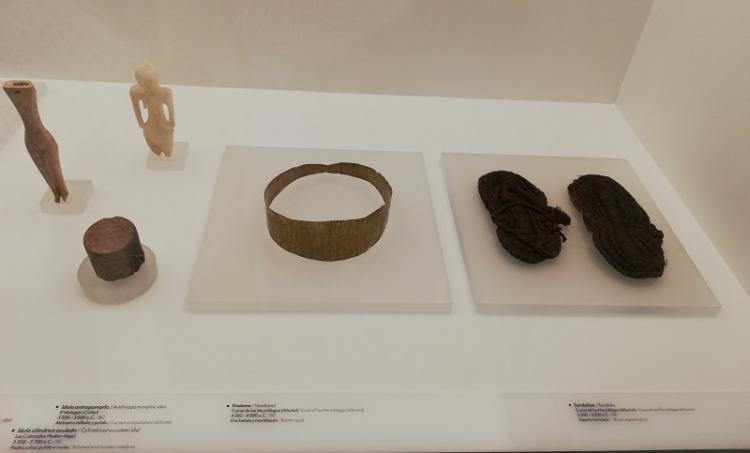 Las sandalias de esparto y la corona de oro encontradas en la Cueva de los Murciélagos de Albuñol, en su vitrina del museo.