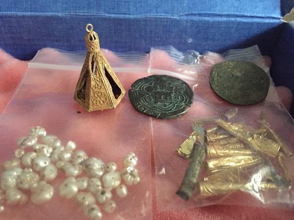 Piezas de oro, monedas y perlas encontradas.
