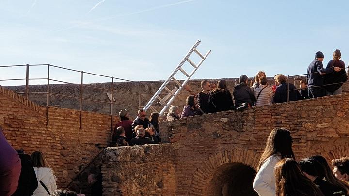 Un empleado de la Alhambra lleva una escalera para arreglar la cuerda de la campana.