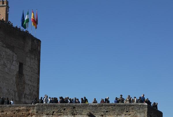 Visitantes pasean junto al Palacio de Carlos V, en el recinto de la Alhambra.