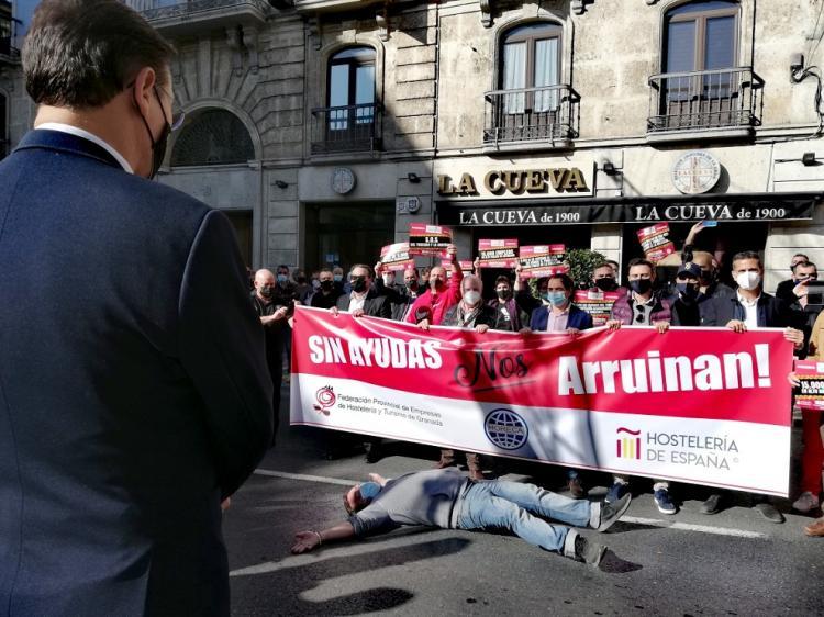 El alcalde observa a uno de los participantes en la manifestación simulando 'la muerte' de la hostelería por el cierre.
