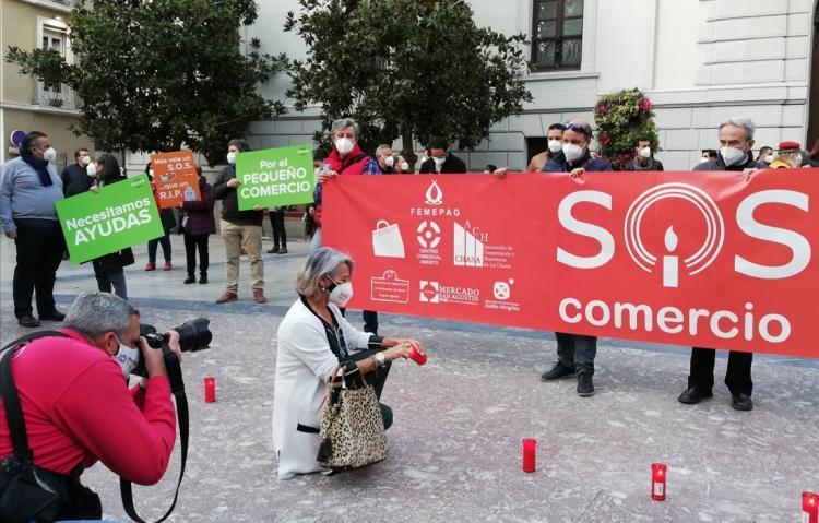 Una comerciante enciende una vela durante la concentración para lanzar un SOS por el sector.
