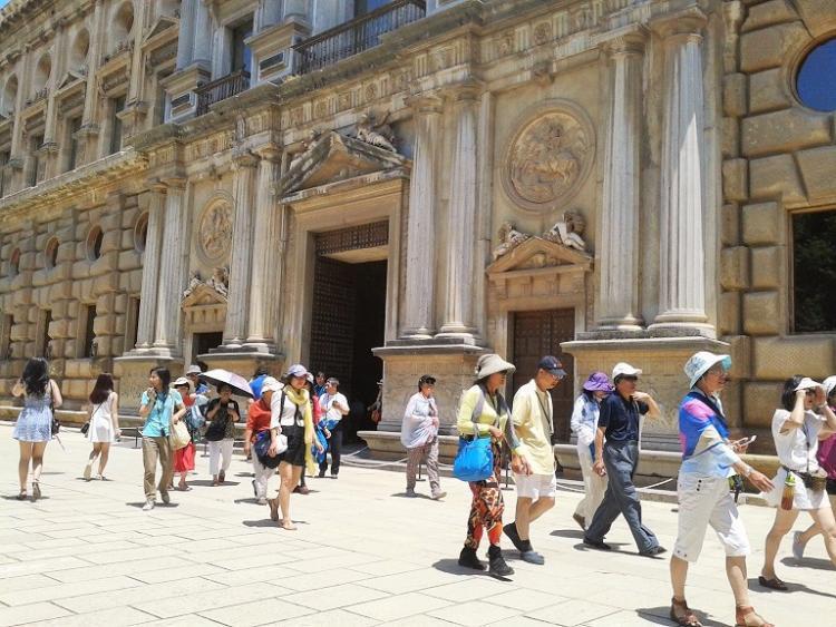 Turistas por la Alhambra se protegen del sol en verano.