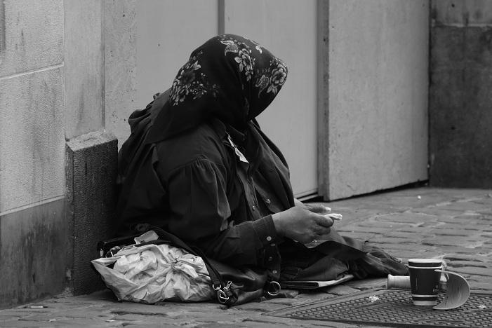 Una mujer pide en la calle.