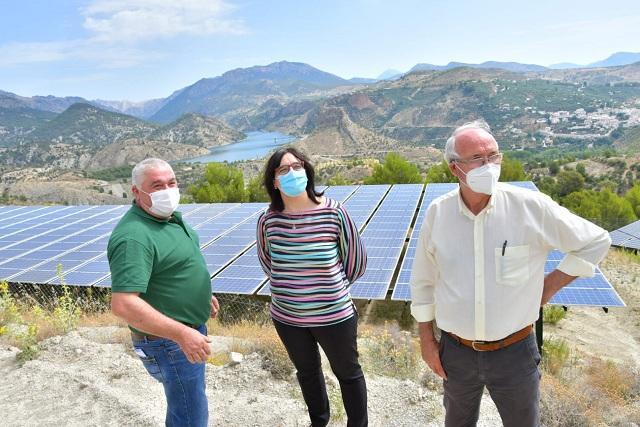Una de las placas solares fotovoltaicas, con el embalse del Portillo al fondo.