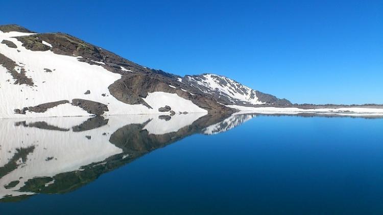 Reflejo de las montañas de Sierra Nevada aún medio nevadas sobre la laguna de las Yeguas.