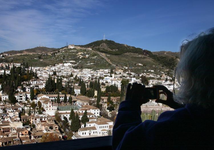 Una turista toma una fotografía del Albaicín.