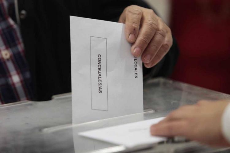 Un elector deposita un sobre electoral en una urna.