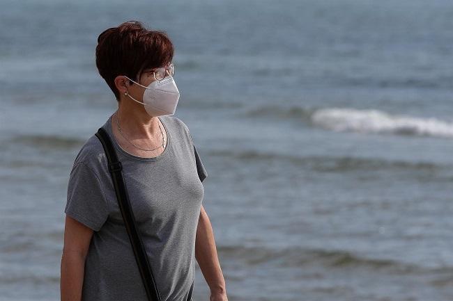 Una mujer con mascarilla pasea por la playa.